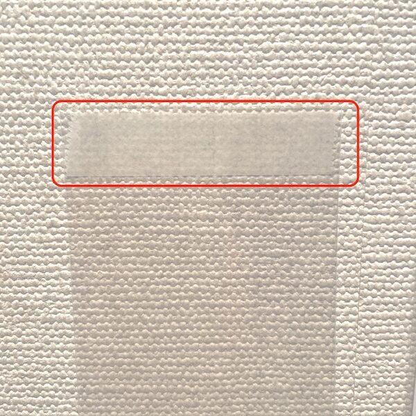 トレーディングカードのポケットを壁に貼って写真を入れる様子